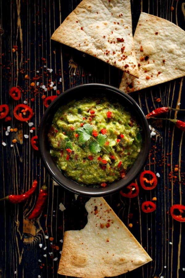 Guacamole is een traditionele Mexicaanse die onderdompeling van avocado, ui, tomaten, koriander, Spaanse peperspeper, kalk en zou royalty-vrije stock fotografie