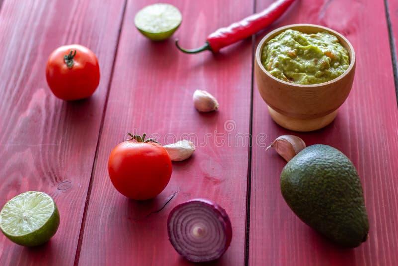 Guacamole i sk?adniki Czerwony t?o kuchnia zielon? meksyka?skiego sosu ostre tacos tradycyjne obrazy stock
