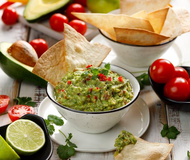 Guacamole, immersion mexicaine traditionnelle faite d'avocat, oignon, tomates, coriandre, poivrons de piments, chaux et sel avec  photo libre de droits