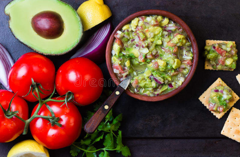 Guacamole latin american mexican sauce in clay bowl and ingredients. Guacamole - latin american mexican sauce in stone mortar and ingredients on dark background royalty free stock photo