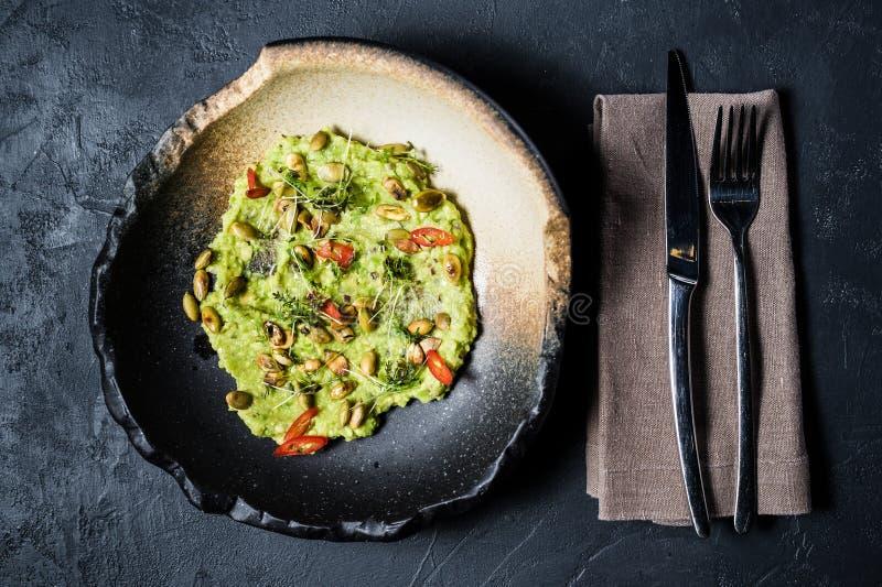Guacamole med grillade jordnötter, svart bakgrund, bästa sikt royaltyfri fotografi
