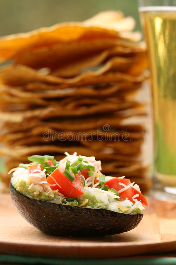 Guacamole Night. Stack of tostados and glass of beer with guacamole in avocado shell stock photography