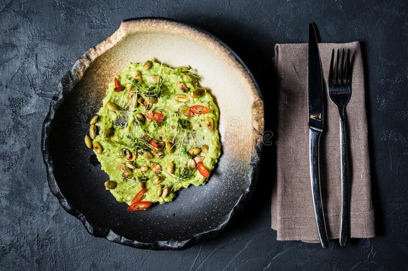 Guacamole with roasted peanuts, black background, top view. royalty free stock photography