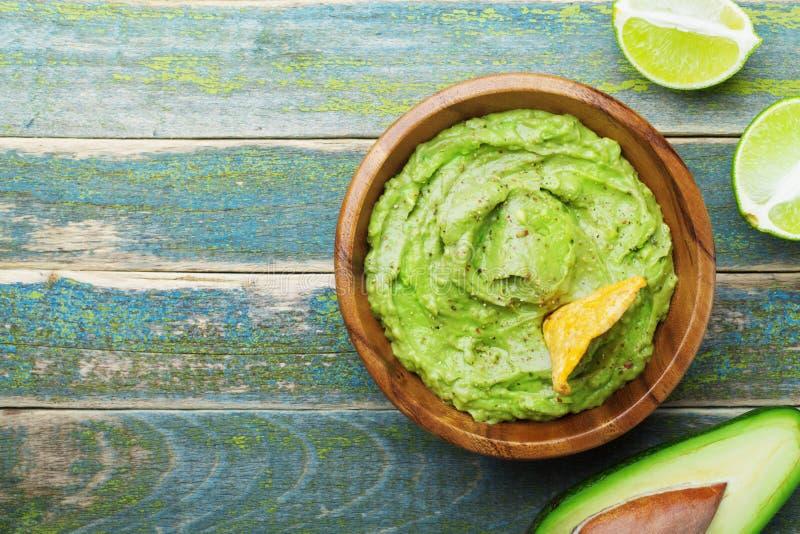 Guacamole verde con gli ingredienti avocado, calce e nacho sulla vista d'annata di legno del piano d'appoggio Alimento messicano  fotografia stock