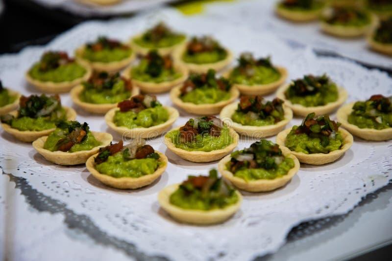 Guacamolebeten op koppen van catering worden gediend die stock afbeelding