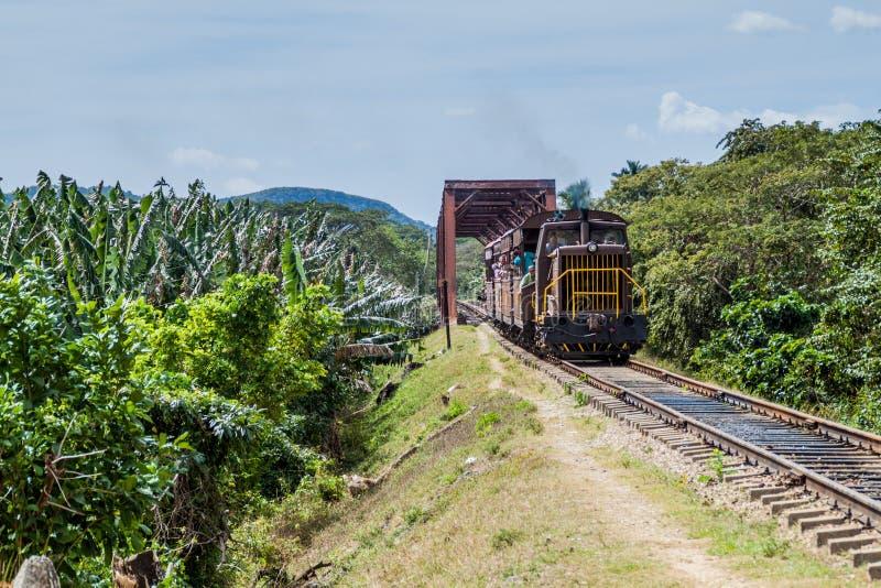 GUACHINANGO, KUBA - 9. FEBRUAR 2016: Nahverkehrszug, der nahe eine Brücke über Ay-Fluss in Tal Valle de Los Ingenios kreuzt lizenzfreies stockfoto