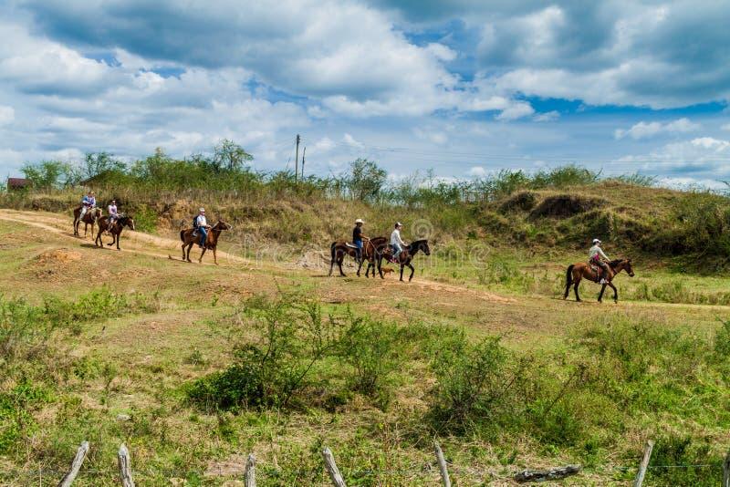 GUACHINANGO KUBA - FEBRUARI 9, 2016: Turister under tur för hästridning i den Valle de los Ingenios dalen nära Trinidad, Cu fotografering för bildbyråer