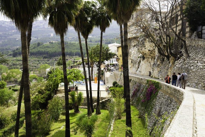 Guadalest, provincia de Alicante España 21 de abril de 2018: La pared del castillo famoso de Guadalest en un lado y las palmeras  fotografía de archivo libre de regalías