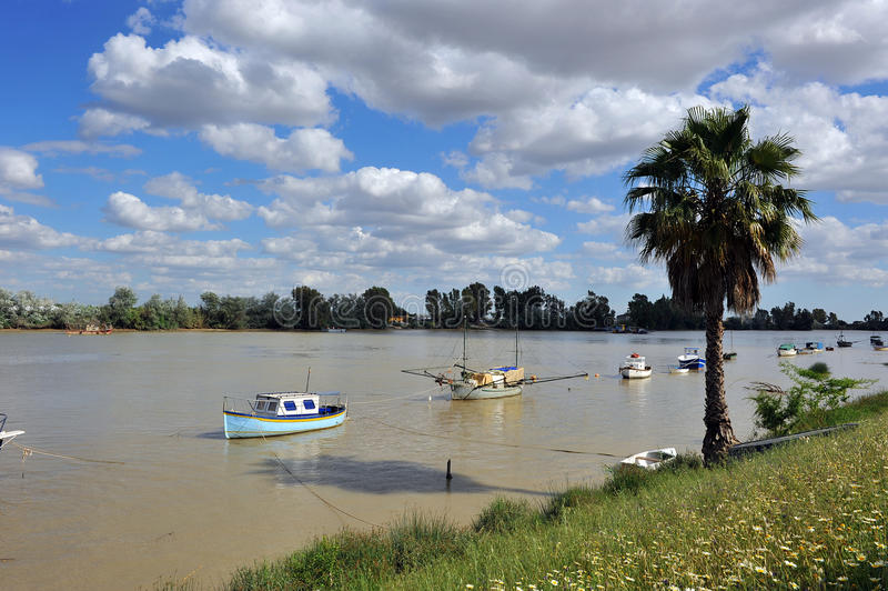 Guadalquivir River as it passes through Coria del Rio, Seville province, Andalusia, Spain. Fishing boats and barges on the River Guadalquivir as it passes stock photos