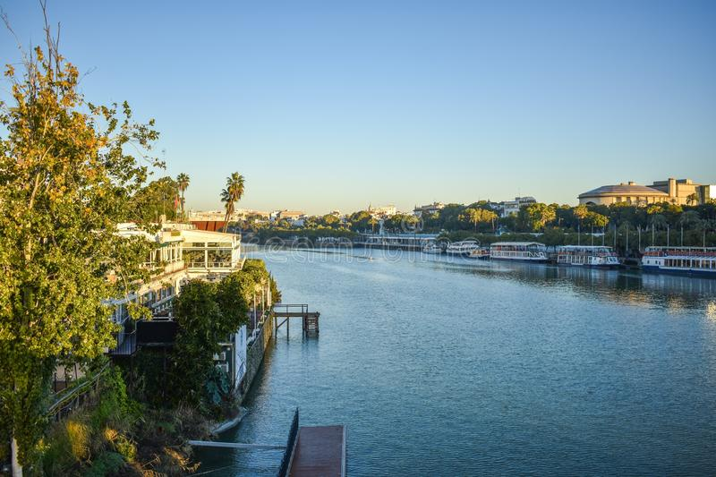 The waterfront of old Seville, Spain. The Guadalquivir river that flows through Seville in the south Spain with riverboats lining the riverfront in the early stock photos