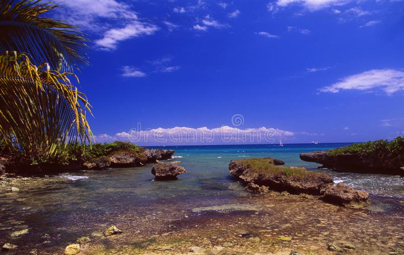 Guadeloupe: coastal landscape with rocks and a sailboat at Bas du Fort stock photos