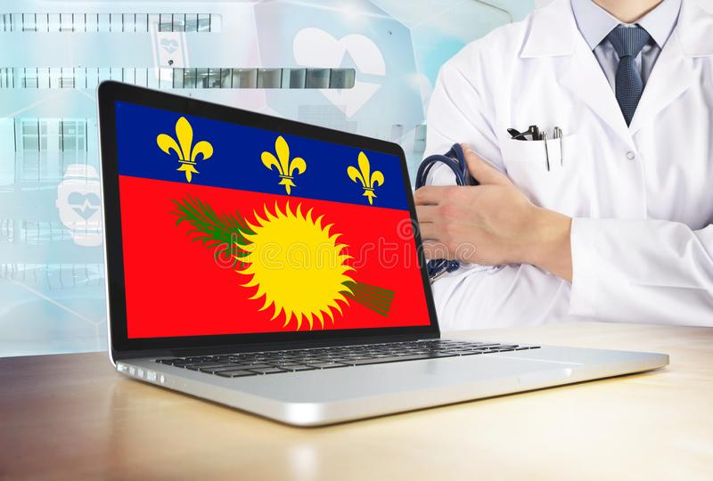 Guadeloupe healthcare system in tech theme. Flag on computer screen. Doctor standing with stethoscope in hospital. Cryptocurrency. And Blockchain concept royalty free stock photo