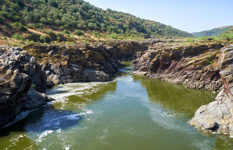 Guadiana river flows through the deep gully in schists. Pulo do. The stream of Guadiana river finds its way through the deep gully in schists at Pulo do Lobo royalty free stock image