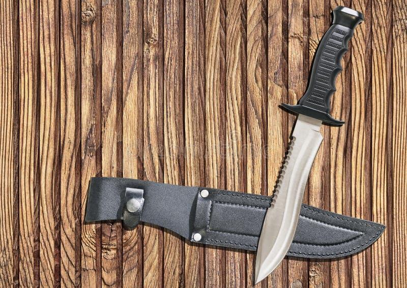 Guaina tattica di Sawback Bowie Knife With Black Leather di sopravvivenza di caccia di combattimento sul vecchio fondo annodato d immagini stock libere da diritti