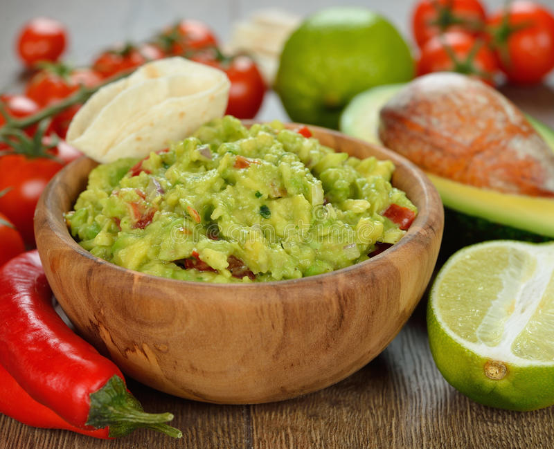 Guakamole. And fresh vegetables on brown background stock image