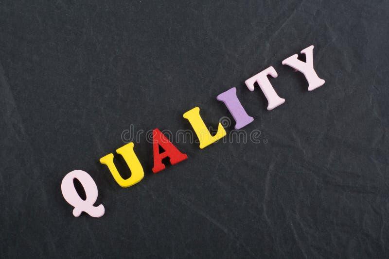 GUALITY słowo na czerni deski tle komponującym od kolorowego abc abecadła bloku drewnianych listów, kopii przestrzeń dla reklama  zdjęcie royalty free