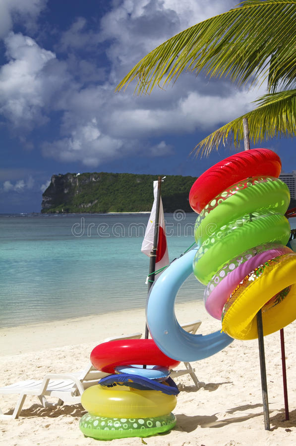 Guam Beach Lifebuoys. Inner tube inflatable life buoys along a beach in Tumon, Guam with Two Lover's Point in the background royalty free stock photography