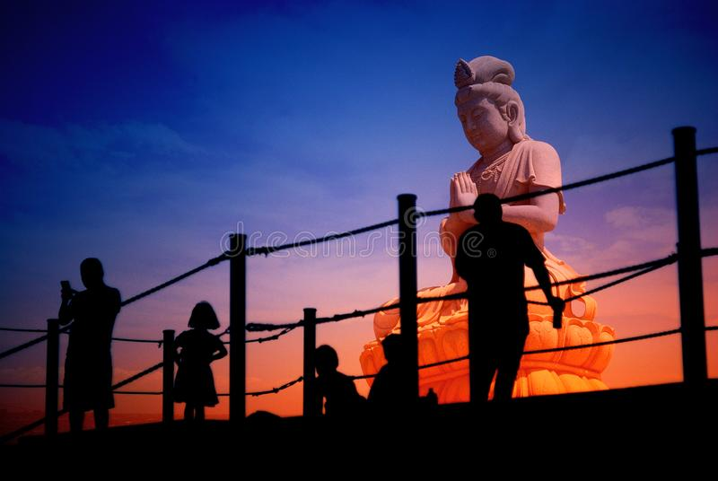 Guan Yin, Guanystin statue, silhouette peoples, holy royalty free stock image