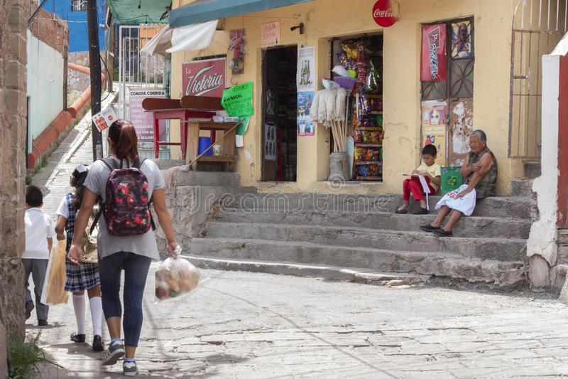 Image of the daily life of Guanajuato at the time of leaving school. Guanajuato, Mexico, September 06, 2018: older woman with a child sitting on the stairs of a stock photo