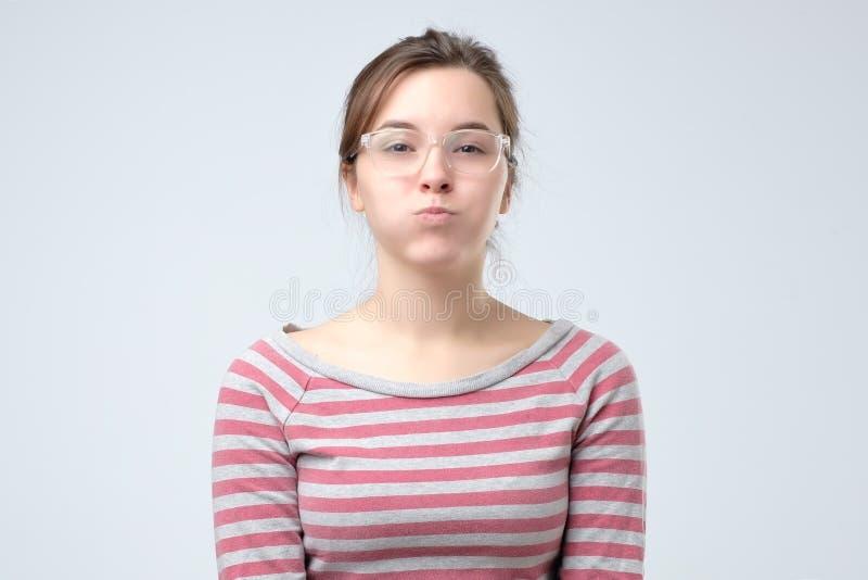Guance di soffio della giovane donna europea, sensibilità infastidite Sta trattenendo il suo respiro fotografie stock libere da diritti