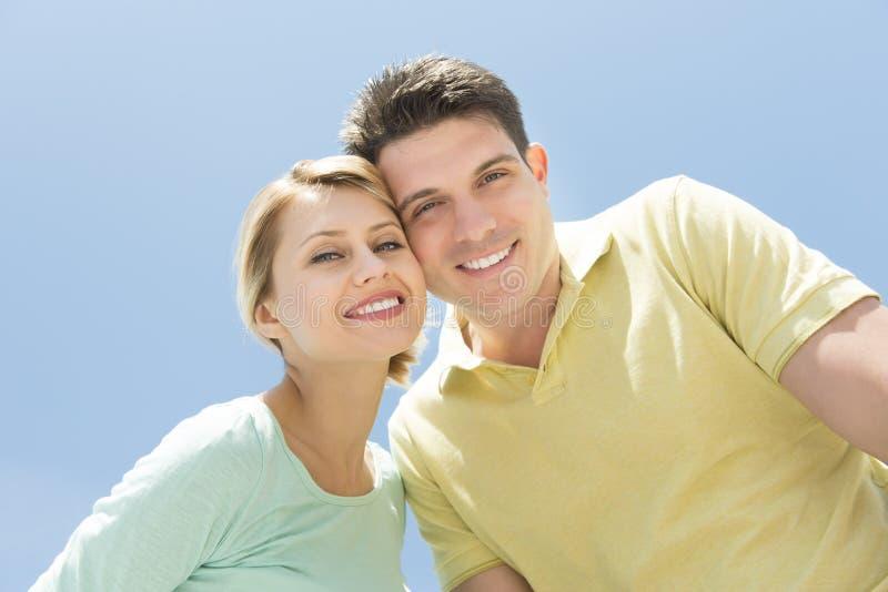 Guancia diritta delle coppie amorose alla guancia contro chiaro cielo blu fotografia stock libera da diritti