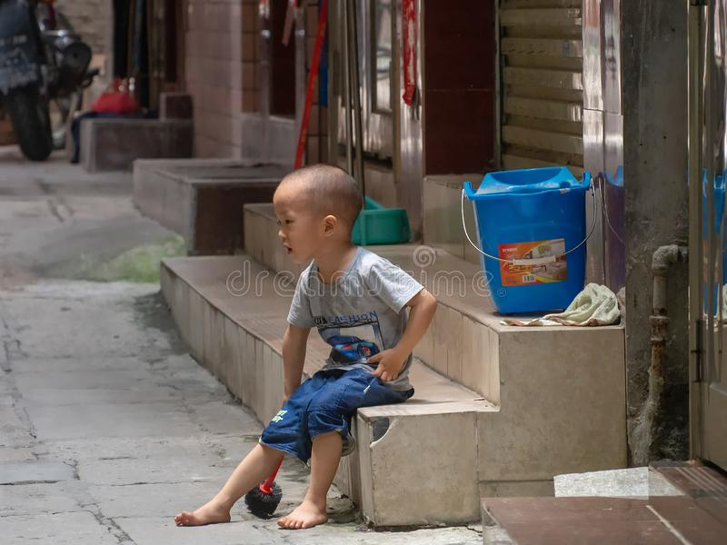 Little Chinese boy playing on a narrow alley of Xiaozhou Village, China stock images