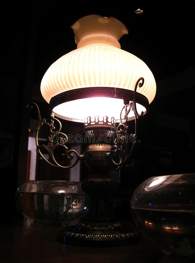 An elegant old-fashioned brass lamp gently shining from the dark corner near my table in the restaurant stock images