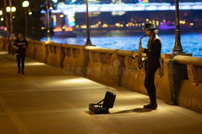 Guangzhou, China - 15. März 2016: bemannen Sie das Spielen des Saxophons auf der Straße am Abend stockfotografie