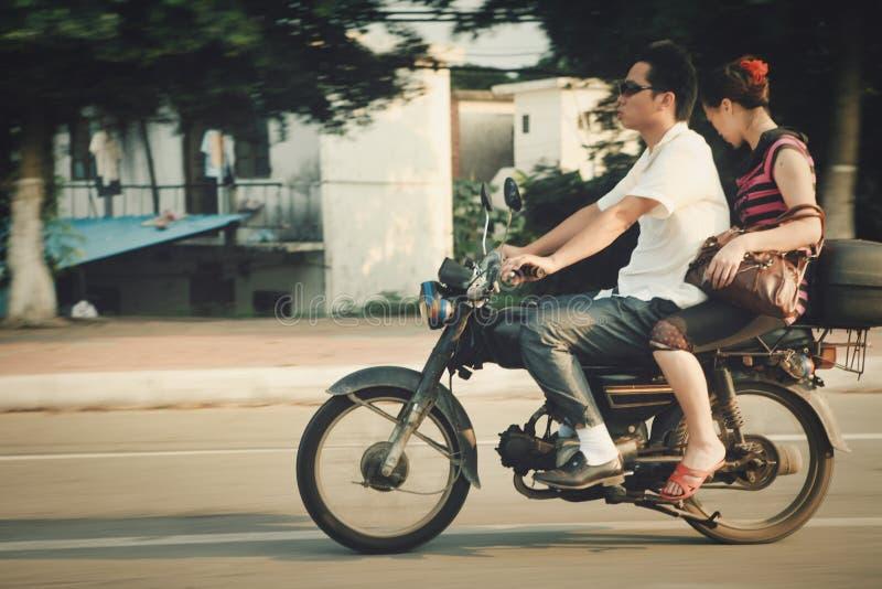 Guangzhou Chiny, Lipiec, - 22, 2018: Mężczyzna i kobieta jedzie motocyklu puszek ulica w Guangzhou obraz stock