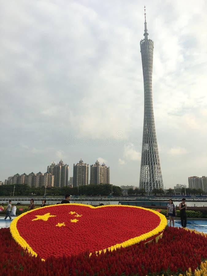 Guangzhou kantontorn med den hjärta formade kinesiska flaggan som göras av blommor arkivfoton