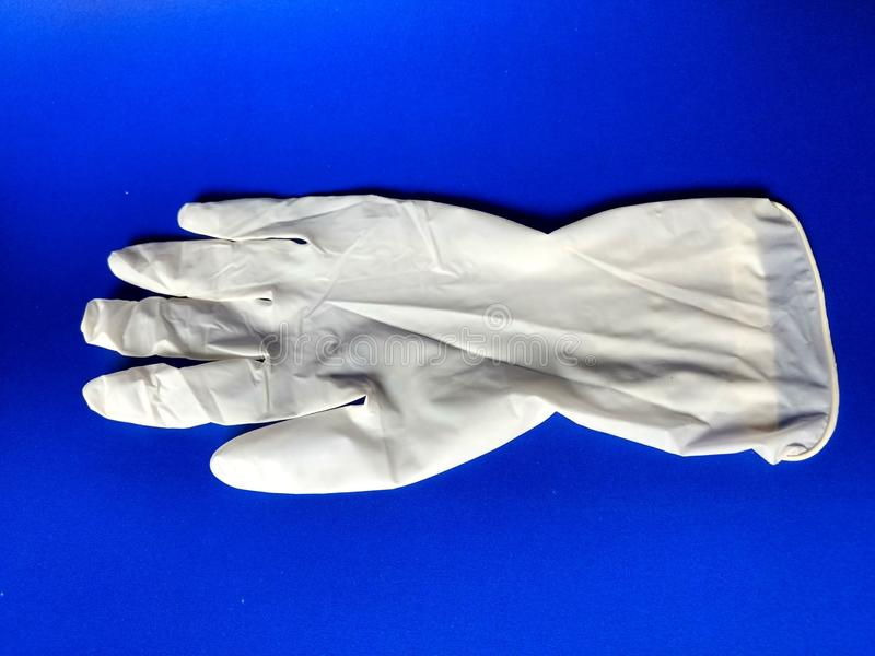 Guante blanco del látex con el fondo azul foto de archivo libre de regalías