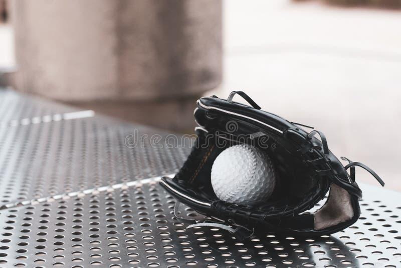 Guante negro del bestball que lleva a cabo un béisbol blanco y colocado en el banco de acero inoxidable imagen de archivo