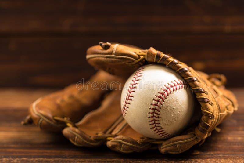 Guante y bola de cuero de béisbol en un banco de madera imágenes de archivo libres de regalías