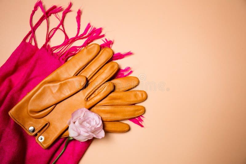 Guantes amarillos en una bufanda rosada imagen de archivo libre de regalías