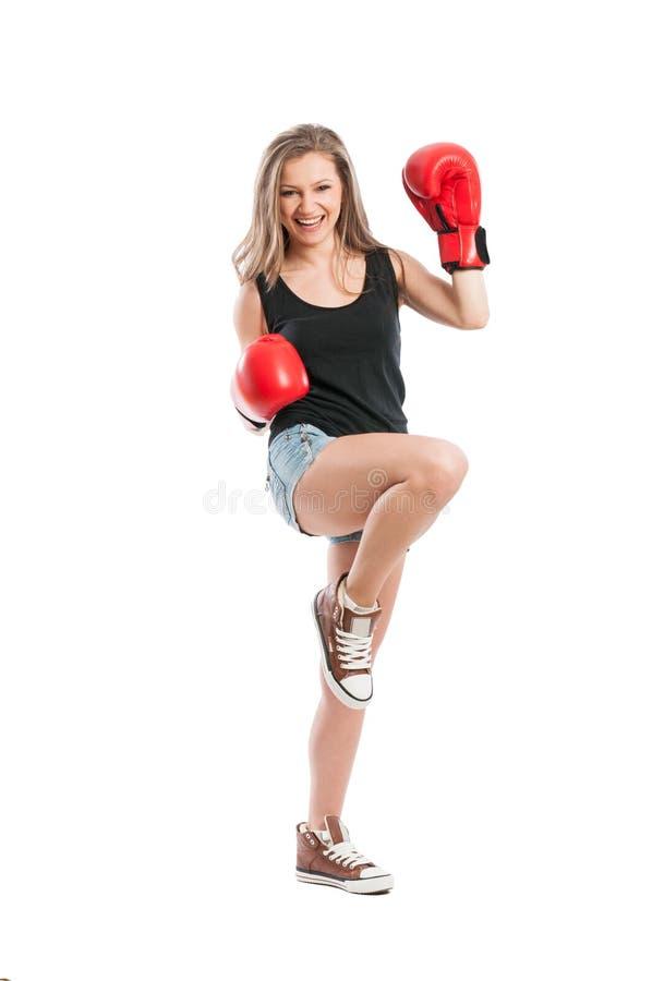 Guantes de boxeo de la mujer joven y pie y mano del aumento que llevan fotografía de archivo