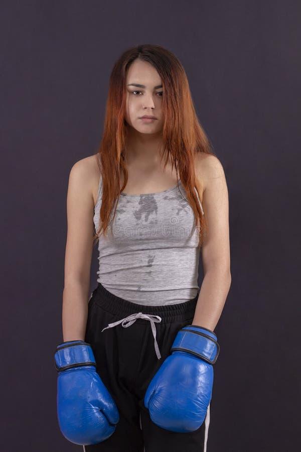 Guantes de boxeo de la muchacha del boxeador digno de cansado y sudoroso imágenes de archivo libres de regalías