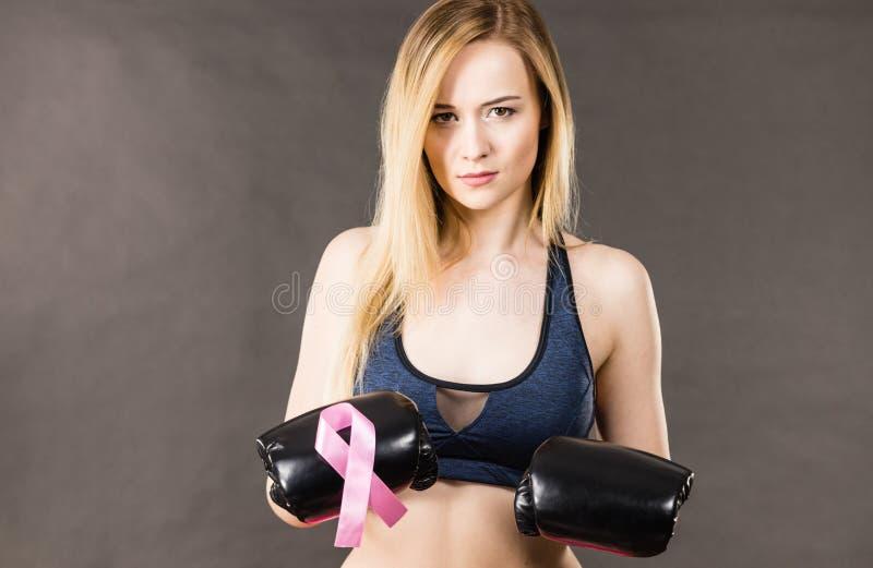 Guantes de boxeo de la mujer que llevan que tienen cinta rosada imagenes de archivo