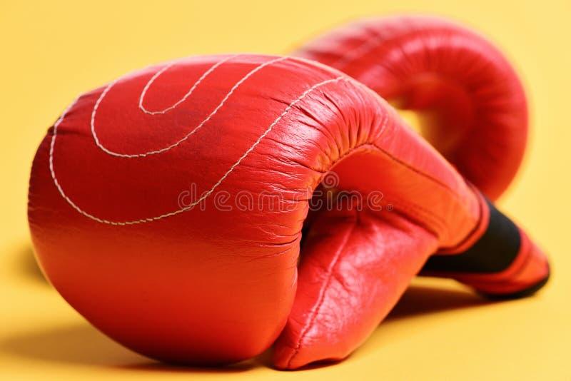 Guantes de boxeo rojos en el fondo amarillo - endecha plana Deportes y concepto del boxeo fotos de archivo