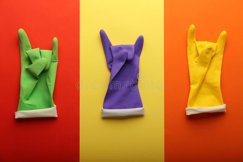 Guantes de goma protectores en el fondo del color, endecha plana imagenes de archivo