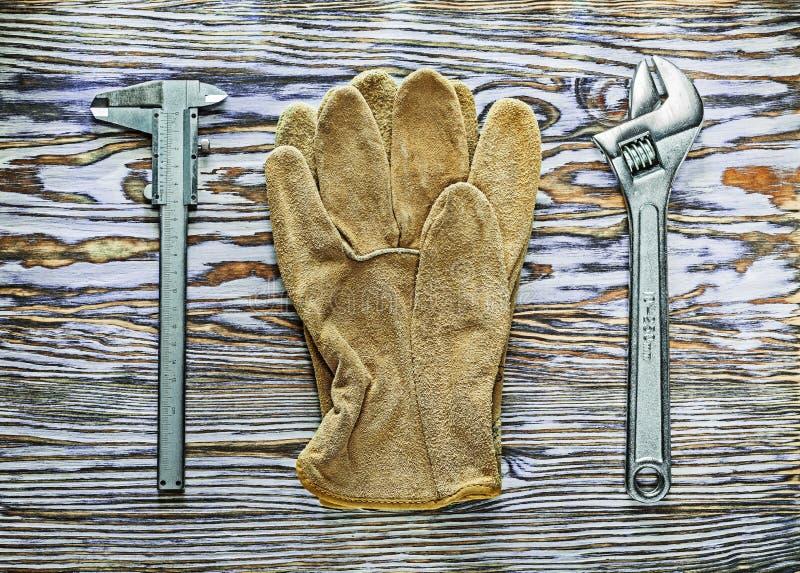 Guantes de la seguridad de la llave inglesa ajustable del calibrador a vernier en el tablero de madera fotografía de archivo