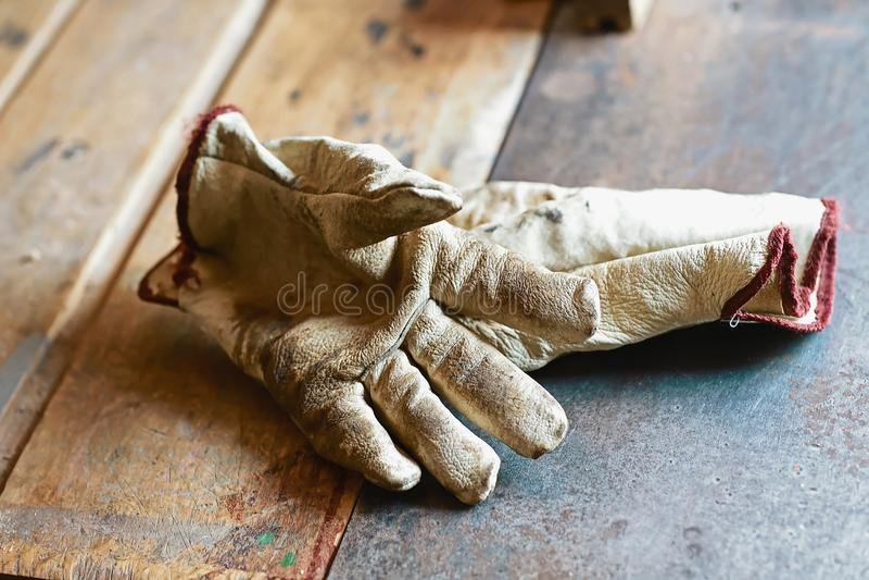 Guantes de trabajo viejos sobre la tabla de madera, en las herramientas del metal de la carpintería de una construcción de la máq imagen de archivo