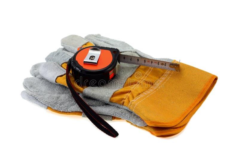 Guantes de trabajo y cinta métrica. foto de archivo libre de regalías
