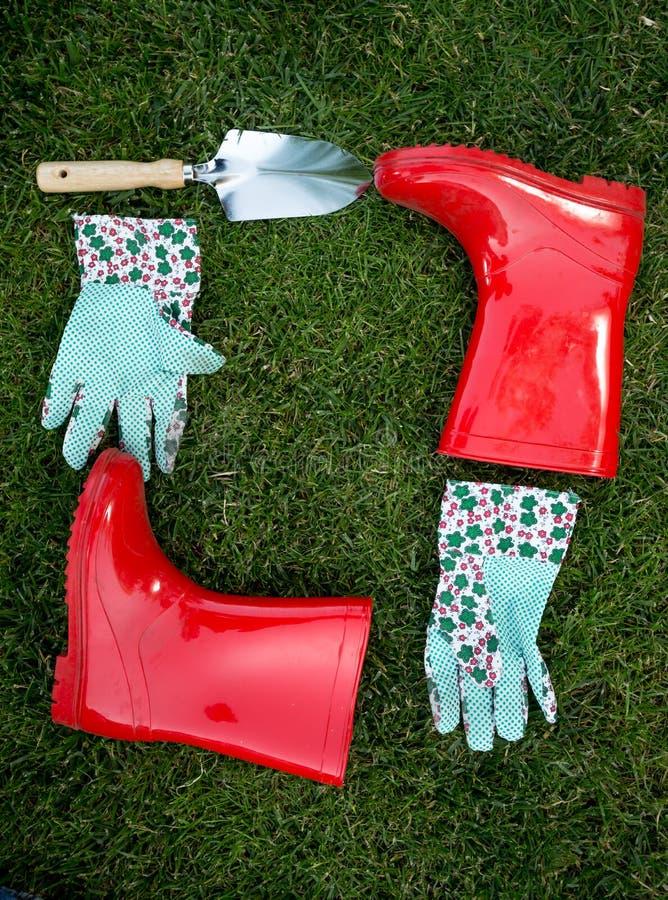 Guantes del jardín, espada y botas de goma rojas mintiendo en hierba verde fotos de archivo