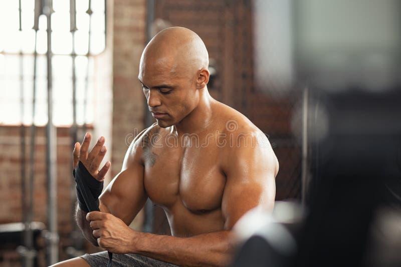 Guantes que llevan del hombre muscular descamisado en el gimnasio imagen de archivo