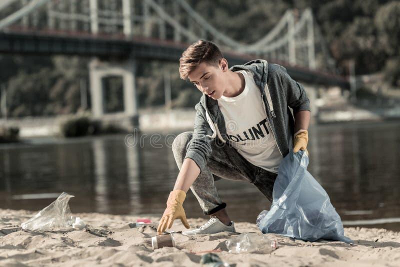 Guantes que llevan del muchacho oscuro-cabelludo apuesto que recolectan las tazas de café vacías en la playa fotos de archivo libres de regalías