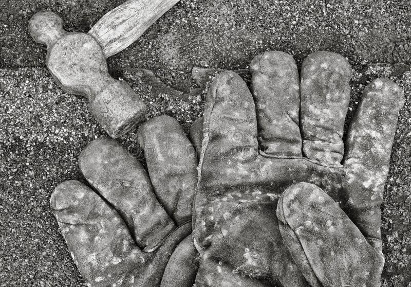 Guantes y martillo del trabajo fotografía de archivo