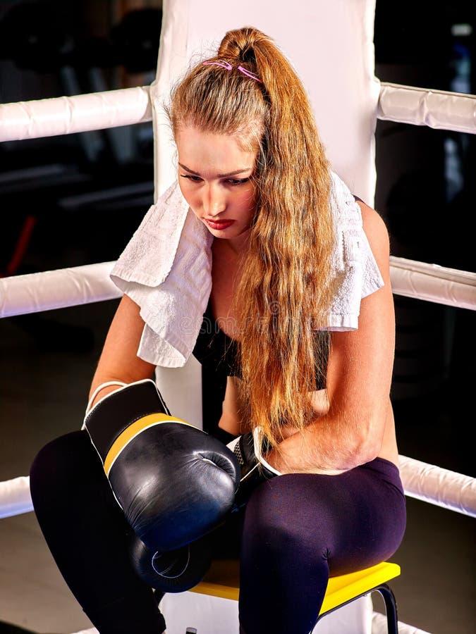 Guanti d'uso di sport della ragazza che si siedono nell'angolo di immagini stock