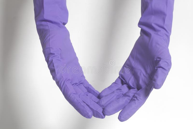 Guanti del lattice per la pulizia sulla mano femminile immagini stock