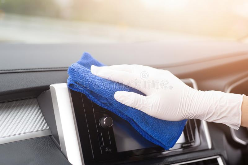Guanti di usura di uomo del lavoratore che puliscono la console interna dell'automobile con il panno del microfiber, dettagliante immagini stock libere da diritti