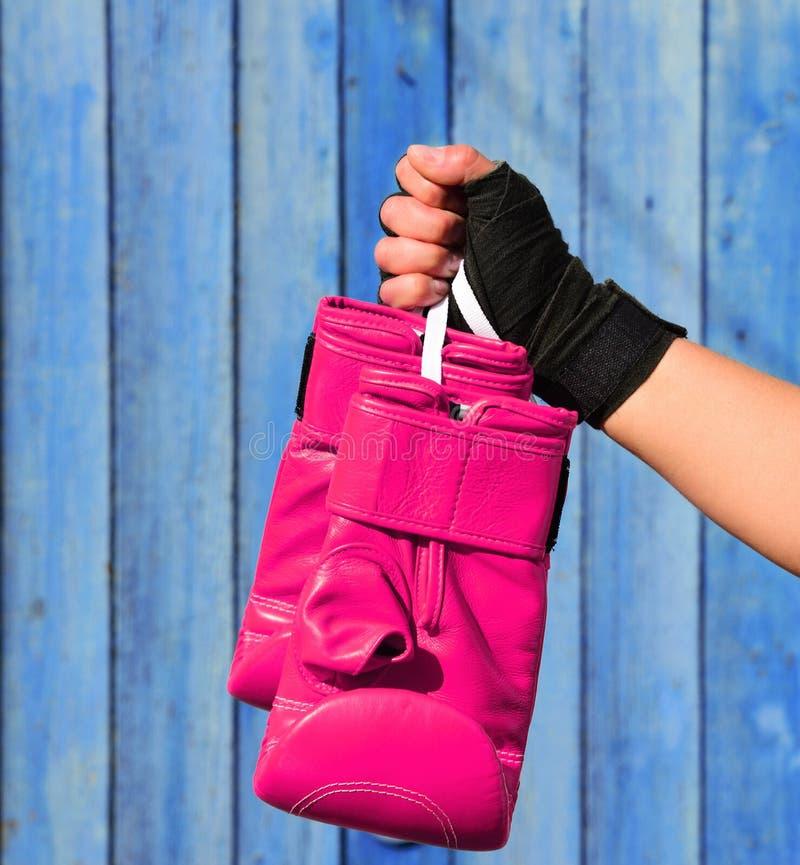 Guanti rosa di cuoio per il kickboxing in mani femminili immagini stock